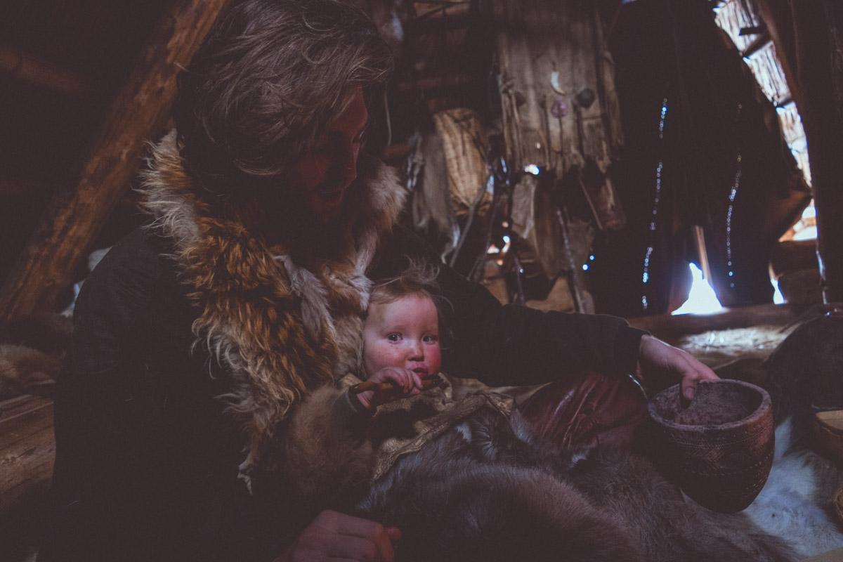 Neolithic man feeding a child