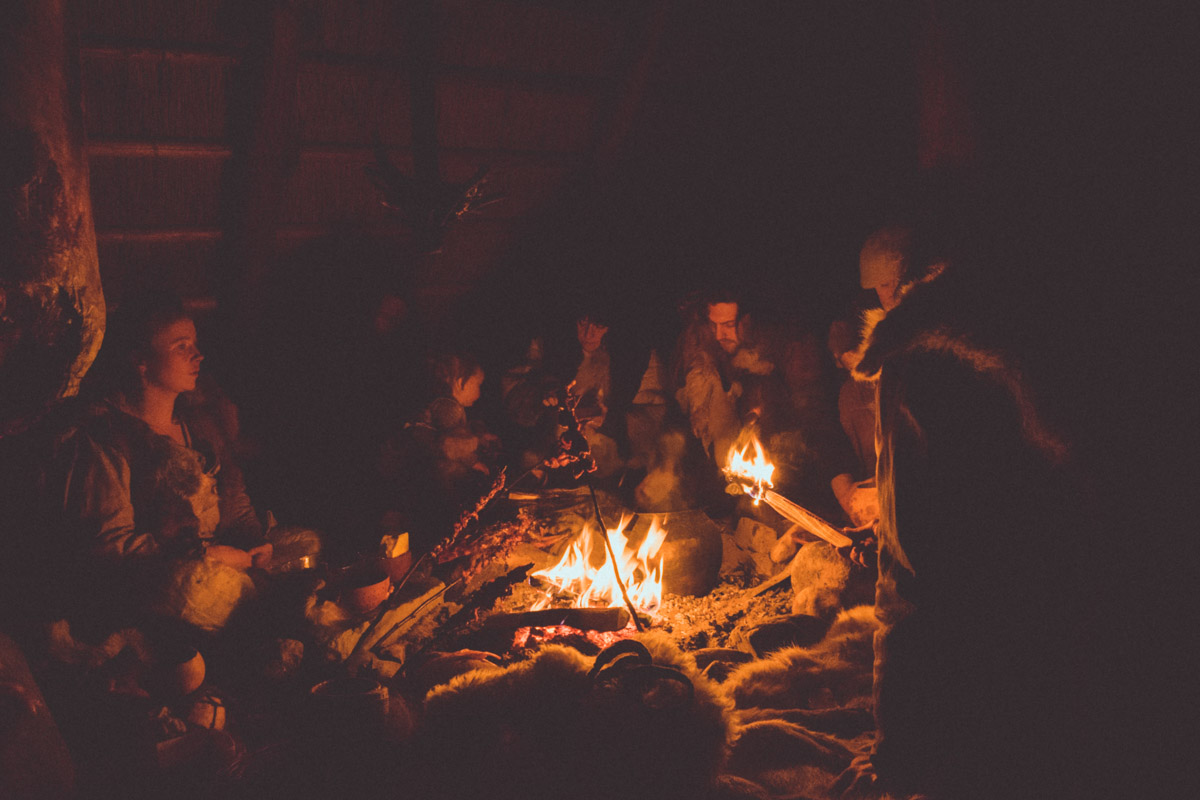 Stone age people sitting by a fire