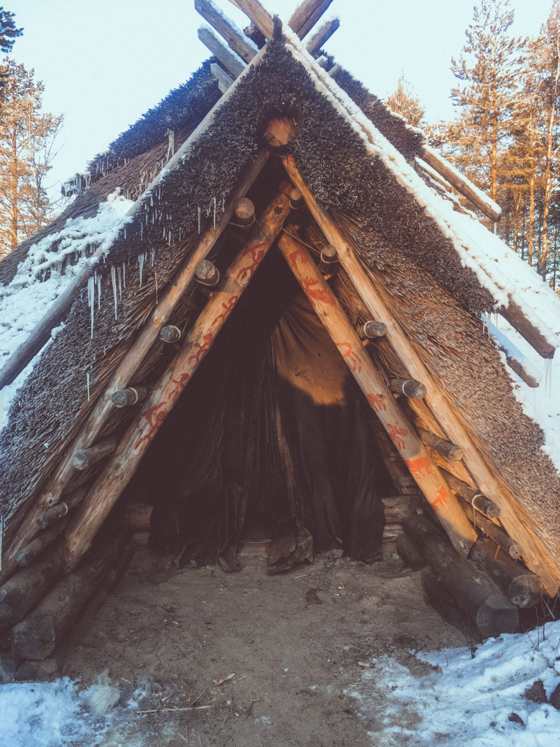 stone age home made of wood and reeds, covered in snow and with the forest in the background